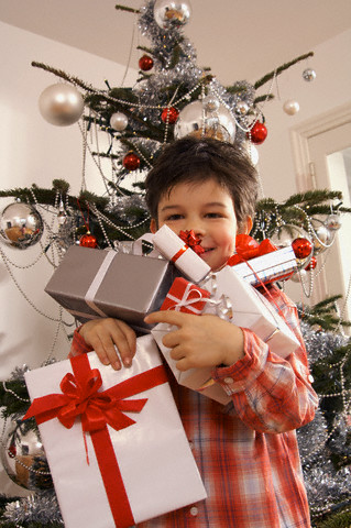 Boy holding many Christmas gifts