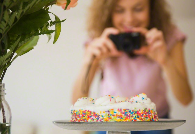 Close up of birthday cake, woman with camera in background