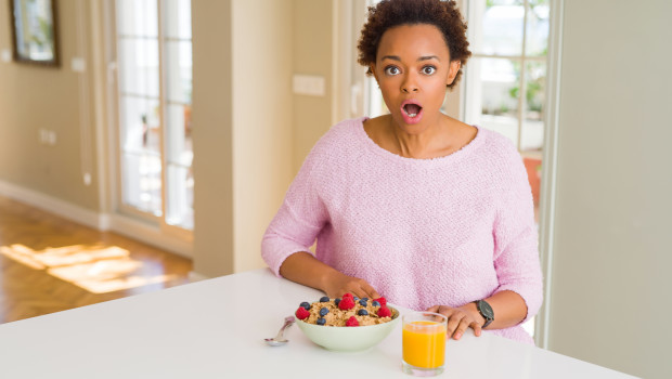 Young african american woman having healthy breakfast in the morning at home afraid and shocked with surprise expression, fear and excited face.