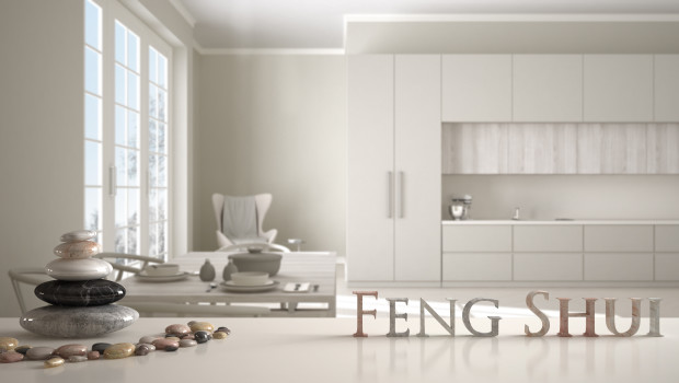 Wooden vintage table shelf with stone balance and 3d letters making the word feng shui over classic beige kitchen with dining table laid for two, zen concept interior design
