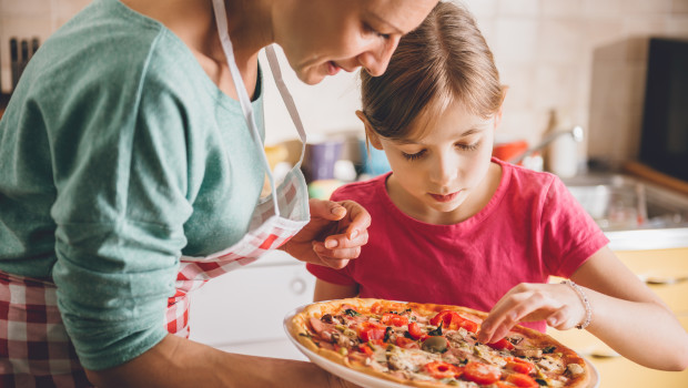 Mother and daughter tasting fresh pizza